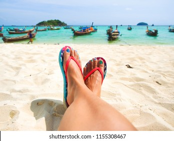 Asian woman tanned leg and feet relaxing on white sand beach with blue sea and wooden boat in background in sunny summer day for vacation holiday concept.