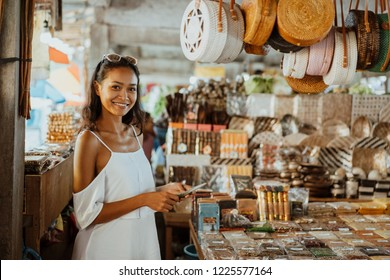 asian woman with tanned skin in the souvenir shop buying some gift