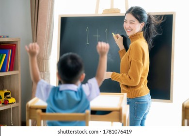 Asian woman teacher and her smart student in class room with backboard background, this image can use for preschool, genius, clever, study, education and school concept.