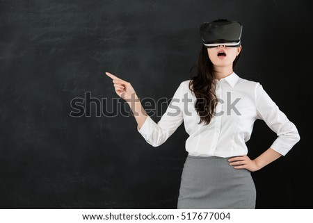 d7cde38fc683 asian woman teacher pointing with virtual reality. VR headset glasses  device. blackboard background.