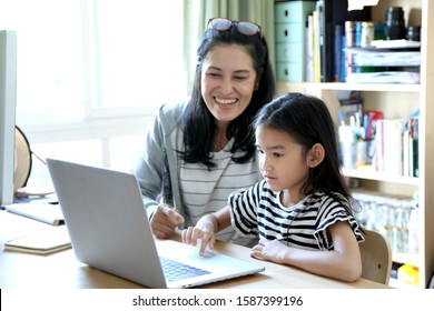 The Asian woman teaching her child to use computer.
