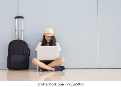 Asian woman teenager using laptop computer at airport terminal sitting with luggage suitcase and backpack for travel in vacation summer relaxing waiting flight transport or booking ticket