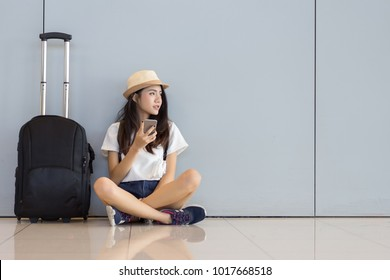 Asian woman teenager using smartphone at airport terminal sitting with luggage suitcase and backpack for travel in vacation summer relaxing waiting flight transport online check in or booking ticket