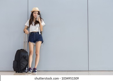 Asian woman teenager using smartphone at airport terminal standing with luggage suitcase and backpack for travel in vacation summer relaxing waiting flight transport online check in or booking ticket
