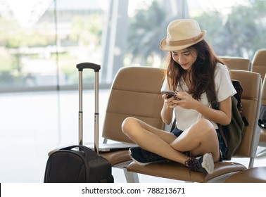 Asian woman teenager using smartphone at airport terminal sitting with luggage suitcase and backpack for travel in vacation summer relaxing waiting flight transport