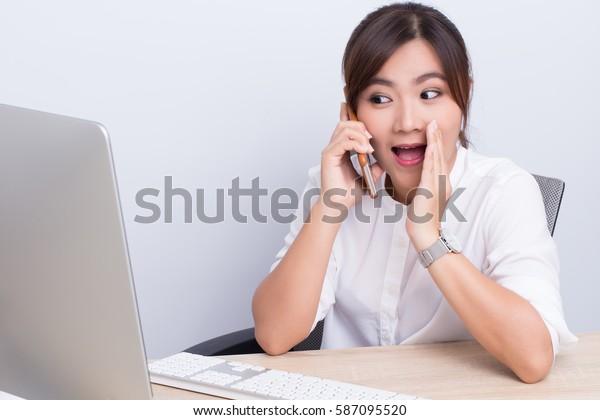 Asian woman telling secret in the office