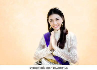 "asian woman in Thai traditional vintage costume siting and greeting action on brown background. Greeting with hand in Thai tradition call ""Sawasdee""."