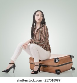 Asian woman thinking and sitting on a luggage.