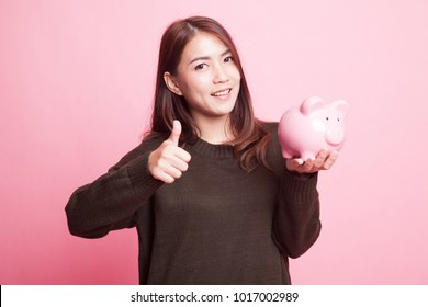 Asian woman thumbs up with pig coin bank on pink background