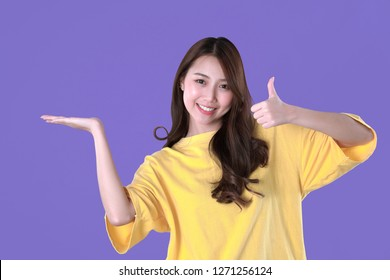 Asian woman thumbs-up for good quality products, yellow t-shirt clothing, purple background