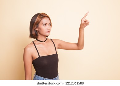 Asian woman touching the screen with her finger on beige background