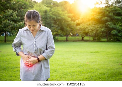 Asian woman touching stomach painful in the right side attack of appendicitis,female patient suffering from stomachache feeling acute pain,appendicitis symptoms,problem with the gut,healthcare concept