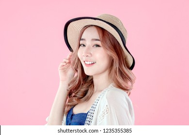 Asian woman tourist happy vacation, summer holiday clothing, pink background