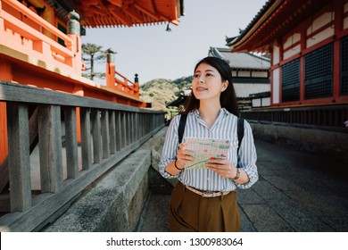 asian woman tourist holding paper map walking sightseeing in kiyomizu dera temple kyoto japan in summer vacation. young girl traveler smiling visiting in japanese red wooden shrine in passage way.