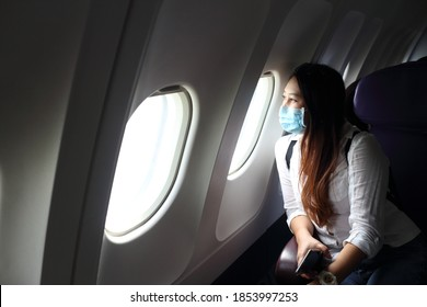 Asian woman tourist on airplane,  medical protective sterile mask on his face traveling. Pandemic covid-19. Safety in public transport.Coronavirus flu virus travel concept