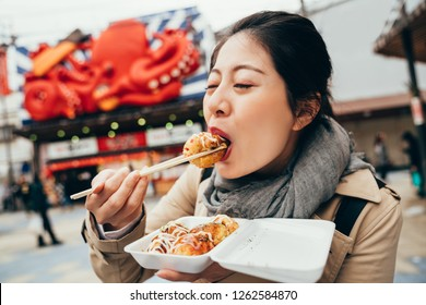 asian woman tourist trying hot takoyaki by chopsticks. young elegant lady standing in front the street vendor shop selling tacoyaki. girl eating delicious octopus balls.