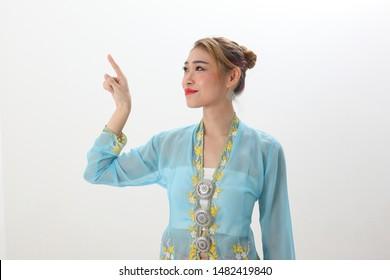 Asian woman traditional blue orange kebaya sharong on white  background pointing finger up