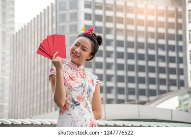 Asian woman in traditional chinese long dress, cheongsam, black hair, carrying Red envelope or gife voucher for reward as a customer for Chinese New Year festival, celebration time