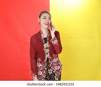 Asian woman traditional maroon kebaya sharong on red yellow paper background talk use phone smartphone
