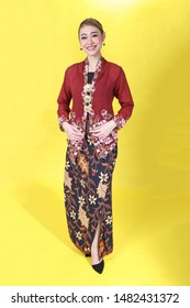 Asian woman traditional red maroon kebaya sharong on yellow paper background posing stand happy
