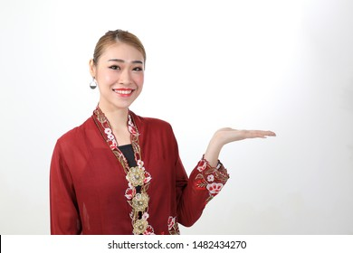 Asian woman traditional red maroon kebaya sharong on white background showing display hand palm