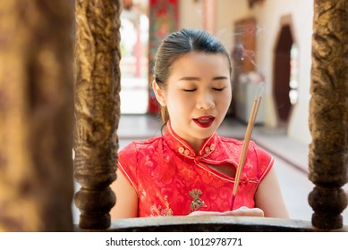 Asian woman in traditional red qipao dress praying with incense sticks during Chinese or Lunar new year in the temple