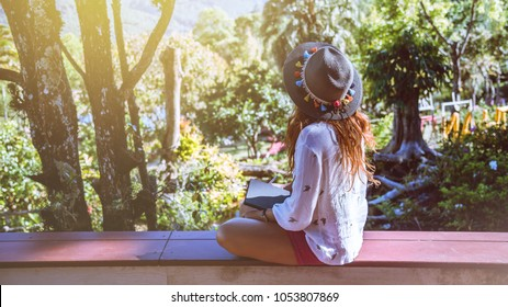 Asian woman travel nature. Travel relax. Study read a book. Nature Education Write a note At public park in summer. In Thailand