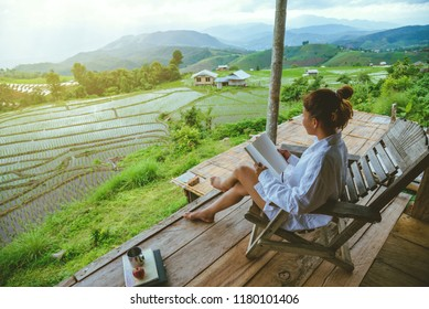 Asian woman travel nature. Travel relax. sit reading book the balcony of the resort. View of the field on the Moutain in summer. Thailand