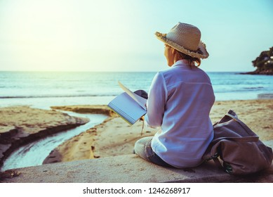 Asian woman travel nature. Travel relax study read a book and write a note on the beach. In the summer. Thailand
