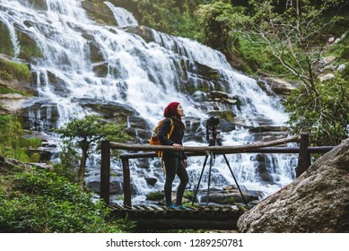 Asian woman travel relax to photograph the waterfalls beautiful. In the winter. at the waterfall mae ya chiangmai in thailand. travel nature. summer