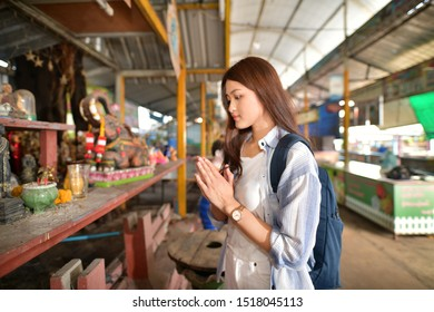 Asian woman traveler backpacker acting Sawasdee or Wai, while traveling to buddhist symbols this is holy