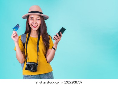 Asian woman traveler holding mobile phone and credit card for online booking and summer travelling concept over blue background
