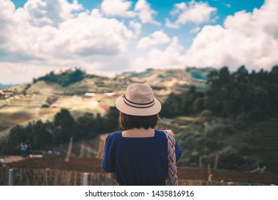 Asian woman traveler looking at amazing mountains and sky, travel holiday relaxation concept.