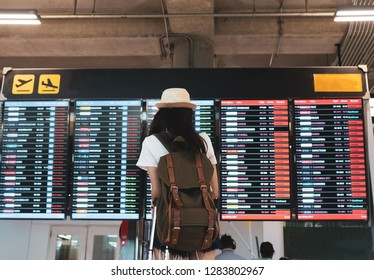 Asian woman traveler looking information board with carrying, suitcase luggage and passenger for tour travel booking ticket flight in airport international vacation time in holiday relaxation.