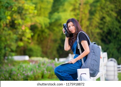 Asian woman Traveler with map backpack relaxing outdoor and listening music with headphones and leave space for adding your content.