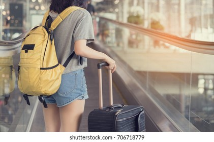 Asian woman traveler standing on elevator with carrying hold suitcase luggage and passenger for tour travel booking ticket flight in airport international vacation time in holiday rest and relaxation.