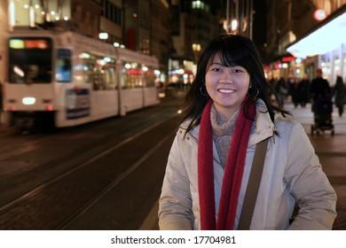 Asian woman traveler walking along the sidewalk of Geneva's shopping district in Switzerland at night.