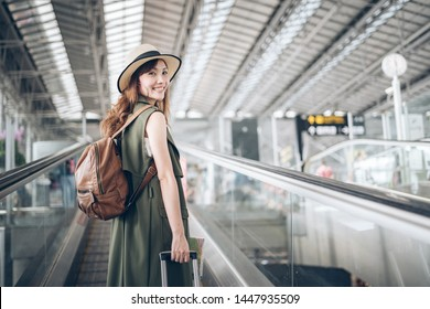 Asian woman traveler walking dragging a suitcase in an airport