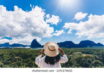 Asian woman traveler wearing a white shirt holding hat and looking at Samed Nang Chee amazing mountains and forest, travel holiday relaxation concept.