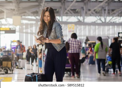 Asian woman traveling by airplane. Traveler preparing her passports and airplane ticket at the airport terminal and airport terminal blurred crowd of travelling people on the background.