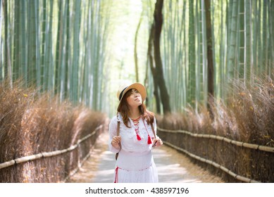Asian woman is traveling into Bamboo forest in Kyoto.