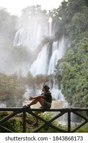 Asian Woman Traveller sitting and enjoy looking to Thi Lo Su (Tee Lor Su) waterfall viewpoint  at the end of the trail, hiking day. the most beautiful and largest waterfall in Tak,Thailand.