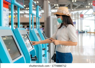 Asian woman traverler wearing mask using self check-in kiosk in airport terminal during coronavirus (COVID-19) pandemic prevention when travel abroad. New normal travel  concept
