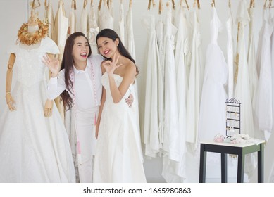 Asian woman is trying on a wedding dress with a smiling face and is well taken care of by the shop owner They look very happy.