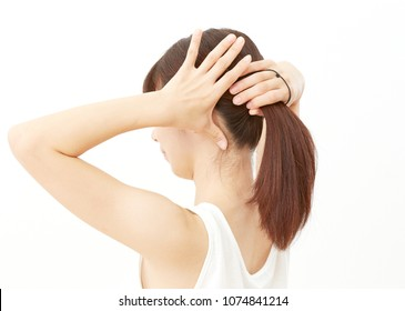 Asian woman tying her hair up