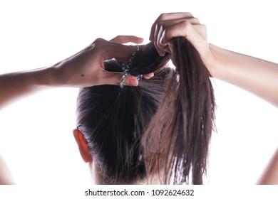 Asian woman tying her hair
