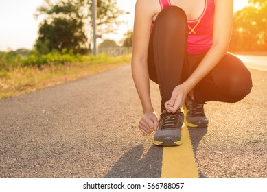 Asian Woman tying shoe before running in sunny nature - sport and people healthy concept