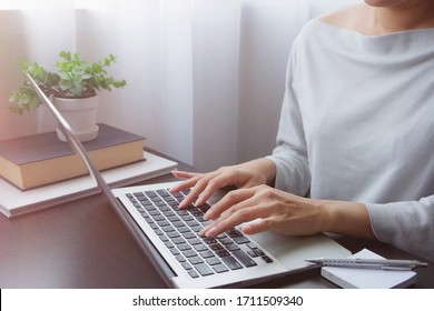 Asian woman is typing on keyboard of laptop or computer notebook for check electronic mail, preparation of presentation in meeting, get information for shopping online or operation of internet banking