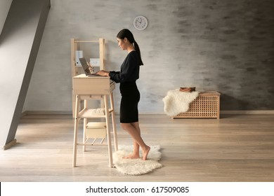 Asian woman typing on laptop at stand-up workplace