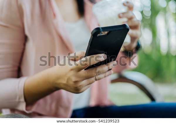 Asian Woman typing text message on smart phone in a cafe. Cropped image of young woman sitting at a chair with a coffee using mobile phone.